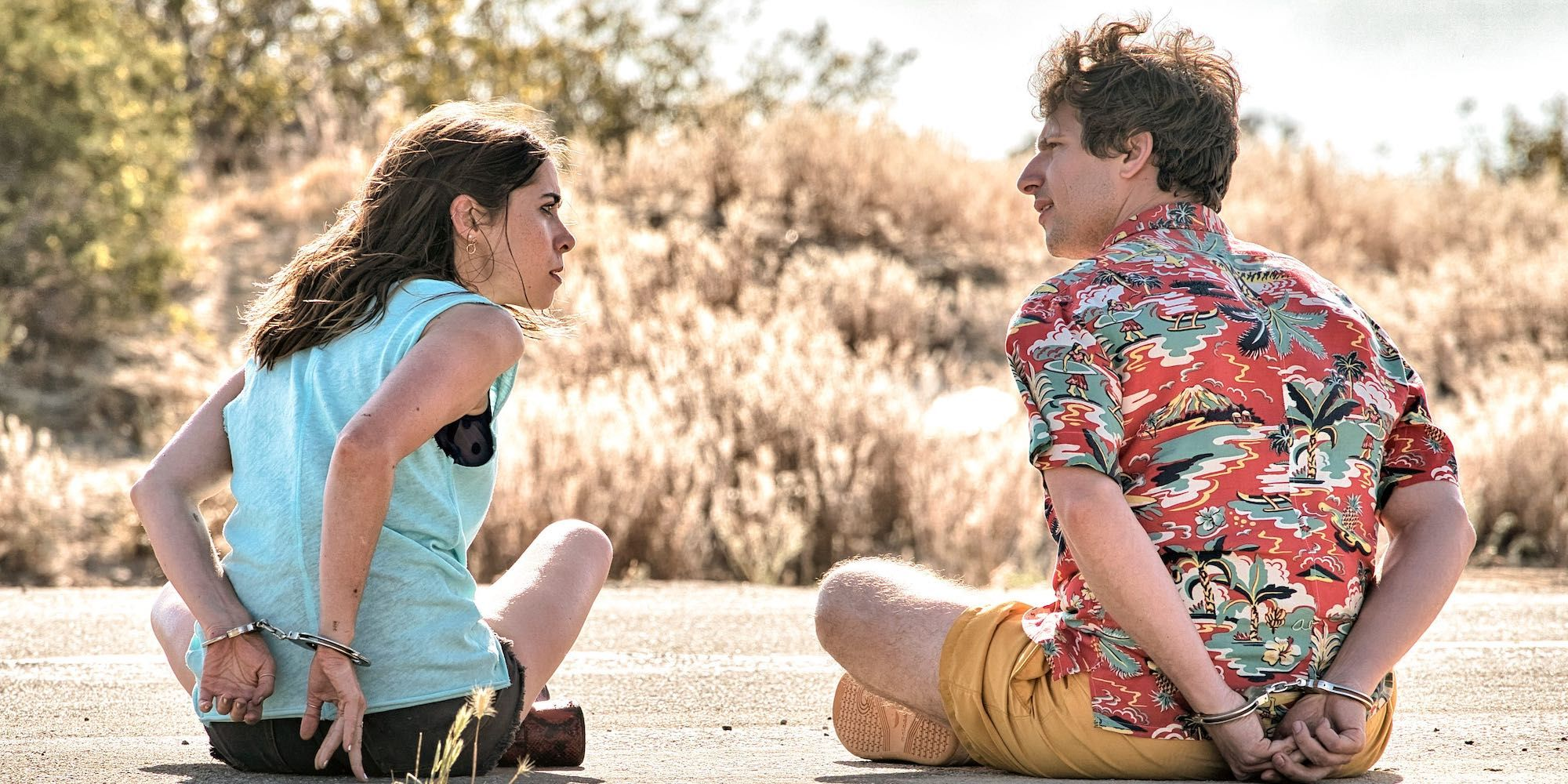 Palm Springs (2020). Sarah (left), a woman with wavy brown hair wearing shorts and a blue tank top sits cross legged on the road beside Nyles (right), who has scruffy brown hair and wears a gharish Aloha shirt and yellow shorts. Both face away from the camera and have their hands cuffed behind they backs.